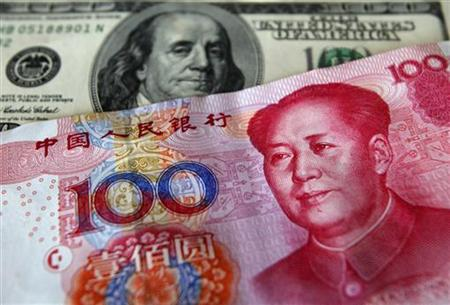 A yuan banknote is displayed next to a U.S. dollar banknote for the photographer at a money changer inside the Taoyuan International Airport