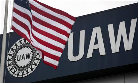 An American flag flies in front of the United Auto Workers union logo on the front of the UAW Solidarity House in Detroit, Michigan, Septemb