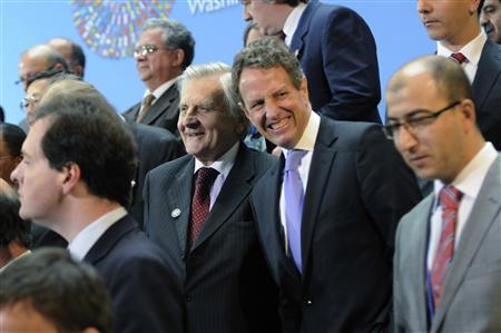 ECB Governor Trichet and U.S. Treasury Secretary Geithner smile as they gather for a group photo during the World Bank/IMF Annual Meetings i