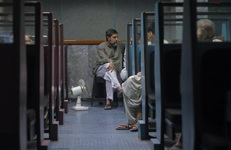 Stockbrokers monitor share prices during a trading session at the Karachi Stock Exchange