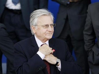 ECB governor Trichet adjusts his tie prior to a family photo taking session at an ECOFIN informal meet in Wroclaw