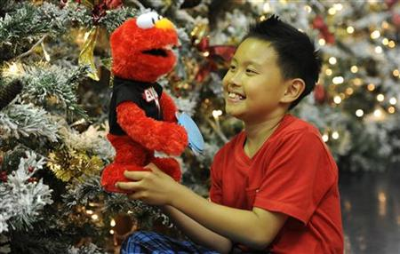 Rio Nguyen, 8, poses for photographers at Hamleys toy store with a Sesame Street Elmo doll in London
