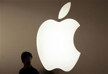 A security guard stands in front of an Apple logo during the inauguration of the company's new store in Nanjing Road, Shanghai