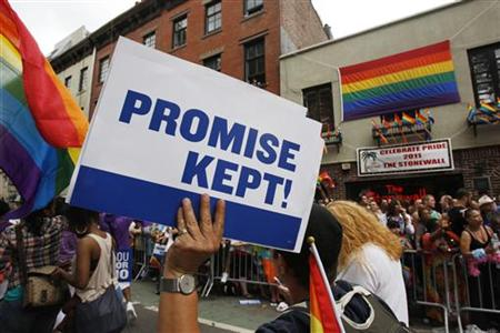 A participant in the Gay Pride Parade holds a sign reading, 'Promise Kept!' in reference to the recent legalization of gay marriage as they