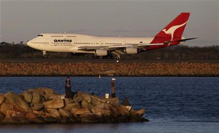 Qantas plane takes off at Sydney's airport as people fish near the runway in Sydney