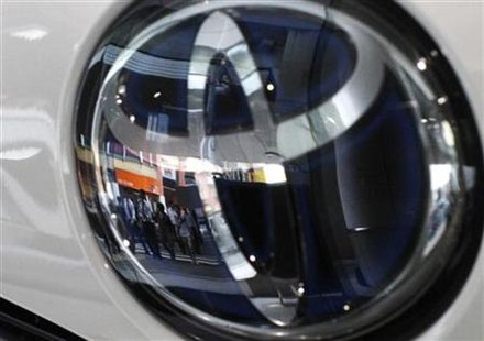 People are reflected on a Toyota Motor vehicle logo at the company showroom in Tokyo