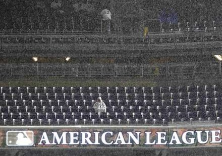 A New York Yankees fan waits during a rain delay in Game 1 of their MLB American League Division Series baseball playoffs against the Detroit Tigers in New York, September 30, 2011. REUTERS