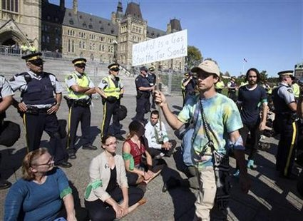 "Demonstrators stage a ""sit in"" after crossing a police barricade during a protest against the Keystone XL pipeline on Parliament Hill in Ott"