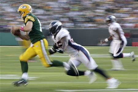 Green Bay Packers' Aaron Rodgers scrambles against the Denver Broncos in the second half during their NFL football game in Green Bay, Wiscon