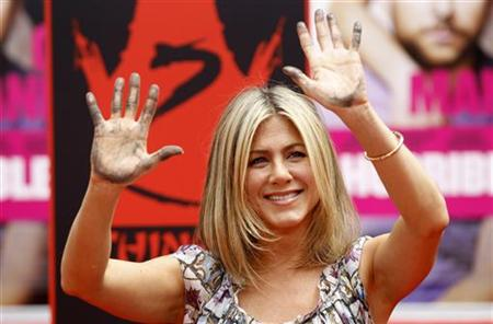 Aniston shows off her hands after leaving her handprints in cement during a hand and footprint ceremony at the Grauman's Chinese Theatre in