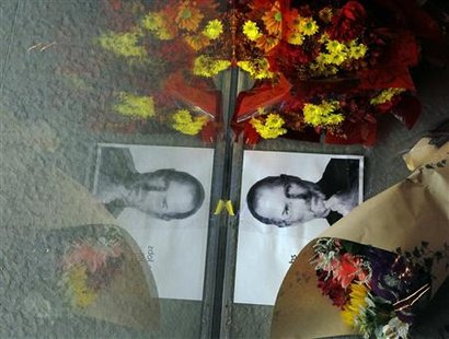 Flowers and a photograph of Steve Jobs are placed against the window outside an Apple store in Boston