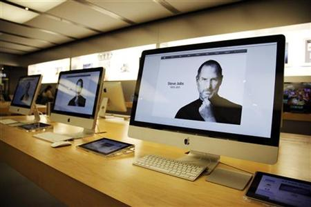 The homepage of apple.com shows the obituary of ex-Apple CEO Steve Jobs on iMac computer screens at an Apple Store in Glendale
