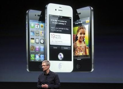Apple CEO Tim Cook speaks in front of an image of an iPhone 4S at Apple headquarters in Cupertino