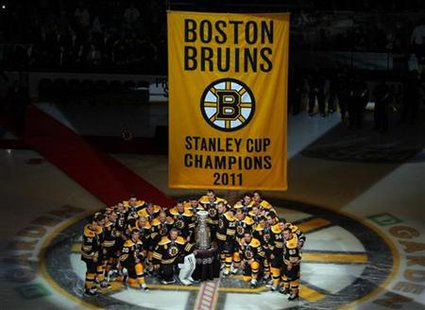 Boston Bruins players pose with the Stanley Cup trophy and their championship banner before taking on the Philadelphia Flyers in the NHL sea