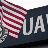 An American flag flies in front of the United Auto Workers union logo on the front of the UAW Solidarity House in Detroit