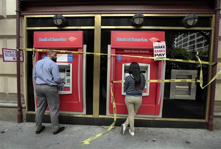 "People use ATM machines at a Bank of America branch after it was occupied during a ""Make Wall Street Banks Pay"" protest march in Los Angeles"