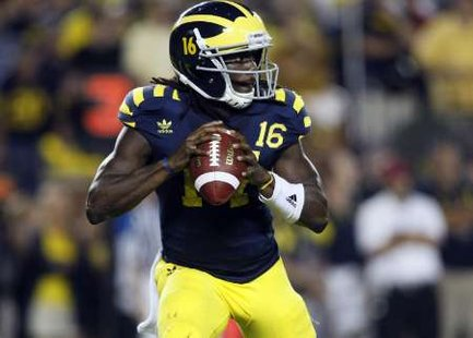 Michigan quarterback Denard Robinson looks for his receiver during the first half of their NCAA college football game against Notre Dame in Ann Arbor, Michigan September 10, 2011. Both teams wore throw back jerseys during the first night game in the history of Michigan Stadium. REUTERS/Rebecca Cook (UNITED SATES - Tags: SPORT FOOTBALL)
