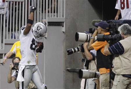 Oakland Raiders' Schilens raises his fist in celebration in the end zone after scoring a touchdown against the Houston Texans during their N