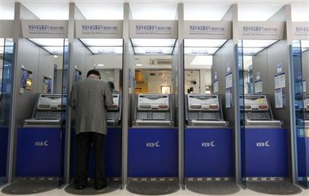 A customer uses an automated teller machine at the headquarters of the Korea Exchange Bank in Seoul