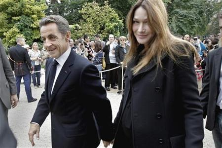 France's President Sarkozy and his wife Carla Bruni-Sarkozy walk in the gardens of the Elysee Palace in Paris during 28th edition of Nationa