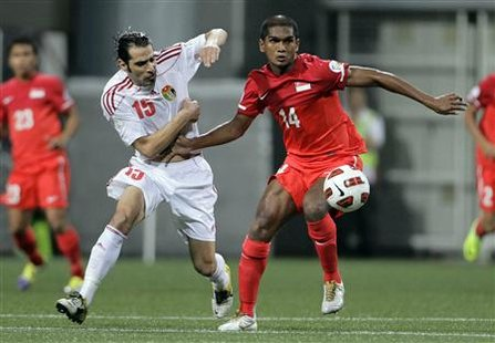 Singapore's Hariss Harun and Jordan's Shadi Abu Hashhash fight for the ball during their 2014 FIFA World Cup qualifying soccer match in Sing