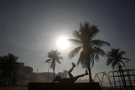 A woman exercises on Leblon beach in Rio de Janeiro