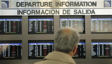 A traveler checks a flight information board at Newark Liberty International Airport