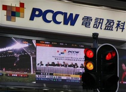 A screen broadcasts a live news feed of an extraordinary general meeting of PCCW outside a PCCW outlet in Hong Kong