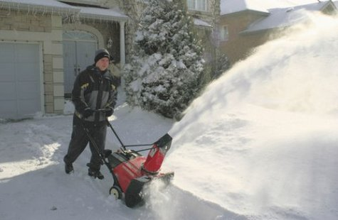Man operating a snowblower.
