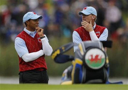 U.S. Ryder Cup players Woods and Stricker stand on the 12th green as they watch other matches at the 2010 Ryder Cup in Newport
