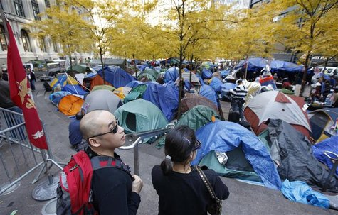 "Tourists look at the ""Occupy Wall Street"" encampment in Zuccotti Park in New York"