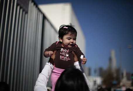 "A woman plays with a baby as they wait to go into a ""Back-to-School"" giveaway at the Fred Jordan Mission in Los Angeles"