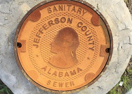A manhole cover bears the logo/design of Jefferson County, Alabama