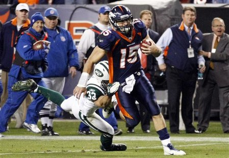 Denver Broncos Tim Tebow runs past New York Jets Eric Smith to score the game-winning touchdown in their NFL football game in Denver