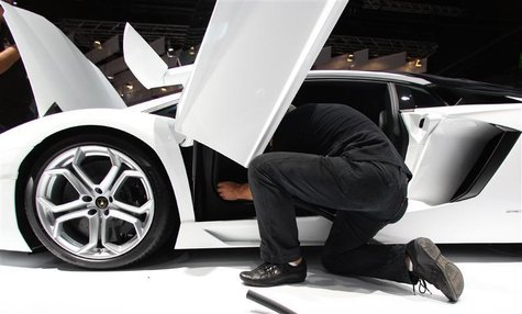 A worker for Italian car manufacturer Lamborghini works on a Lamborghini Aventador during preparation work for the IAA in Frankfurt