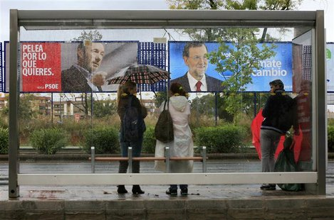 People wait in front of electoral posters at a bus stop in Seville