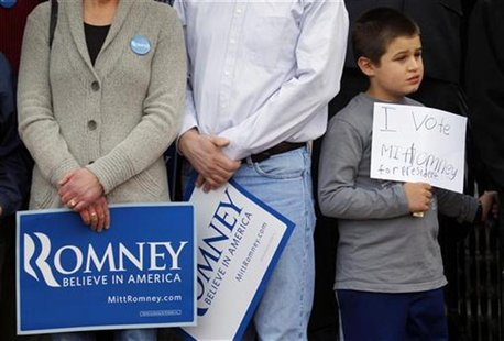 A young supporter holds a handwritten sign for Republican presidential candidate Romney at a campaign rally in Nashua