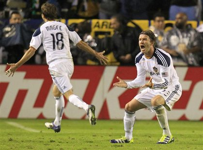 Los Angeles Galaxy's Beckham celebrates with Magee after teammate Donovan scored against the Houston Dynamo during the MLS Cup soccer final