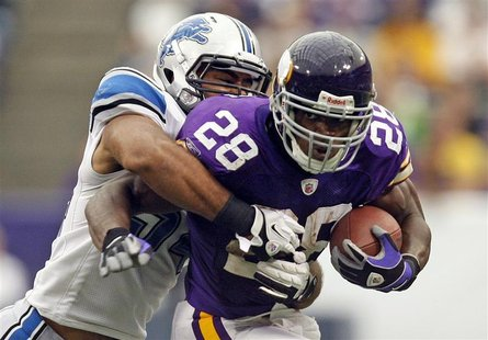 Minnesota Vikings running back Peterson is tackled by Detroit Lions line backer Levy during their NFC football game in Minneapolis