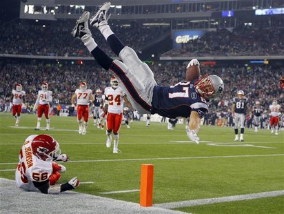 New England Patriots tight end Rob Gronkowski (top) scores a touchdown over Kansas City Chiefs linebacker Derrick Johnson in the second half