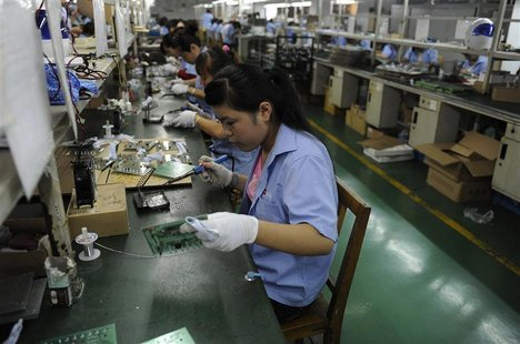 An employee works on circuit boards at an electronic component factory in Hefei