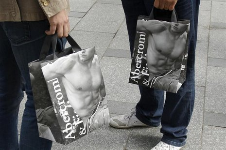 Shoppers hold bags with clothing purchases on the opening day of operations by retailers Abercrombie & Fitch outside their Paris store