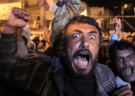 Anti-government protesters react as they celebrate the signing by Yemen's President Ali Abdullah Saleh of a deal to step down in Sanaa