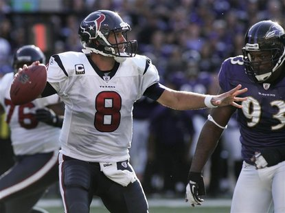 Texans' Schaub looks to pass the football as he gets chased out of the pocket by Ravens' Redding during their NFL football game in Baltimore