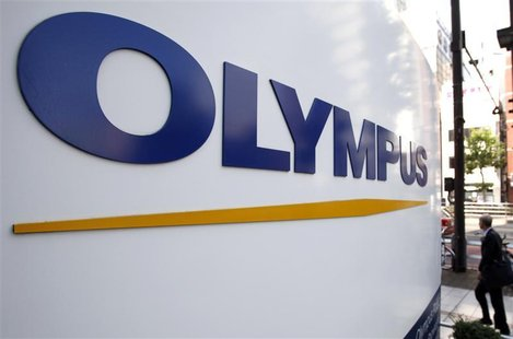 A man walks past a sign of Olympus Corp outside the company's showroom in Tokyo