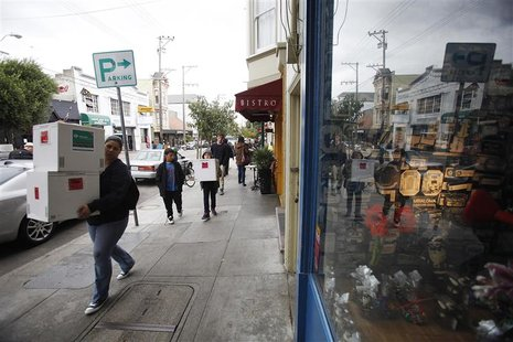 People carrying boxes walk past Chocolate Covered candy shop in the Noe Valley district in San Francisco