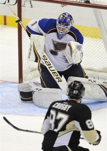 St. Louis Blues goalie Brian Elliott makes a stick save against the Pittsburgh Penguins Sidney Crosby in their NHL hockey game in Pittsburgh