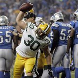 Green Bay Packers full back John Kuhn spikes the ball after scoring a touch down against the Detroit Lions during the second half of their N