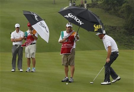 McIlroy of Ireland and teammate McDowell stand under umbrellas in the rain on the sixth green during the third day of the Mission Hills Worl