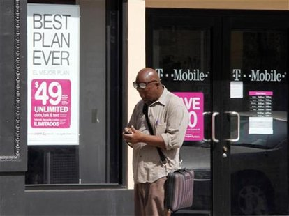 A man checks his mobile phone as he walks past a T-Mobile store in downtown Los Angeles
